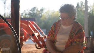 Ruth Kinard sits with her husband Richard at the wood shed catching up on their daily activities.